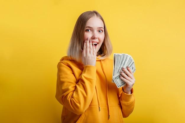 Mulher jovem rica e animada feliz ganhar dinheiro em espécie. senhora segura pilha de dólar surpreso se alegra com a vitória da loteria. menina adolescente cobriu a boca aberta com a mão surpresa isolada sobre a parede de cor amarela.