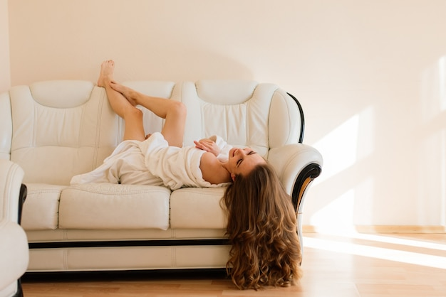 Mulher jovem rica e feliz usando um robe noturno em uma janela grande no quarto, olhe para fora e desfrute da vista dos sonhos
