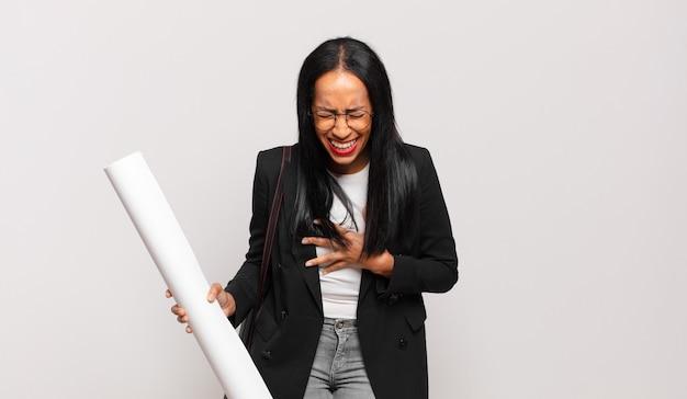 Mulher jovem rindo alto de uma piada hilária, sentindo-se feliz e alegre, se divertindo
