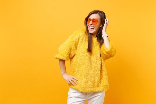 Mulher jovem rindo com os olhos fechados, no suéter de pele e óculos coração laranja, colocando a mão na cabeça isolada em fundo amarelo brilhante. emoções sinceras de pessoas, conceito de estilo de vida. área de publicidade.