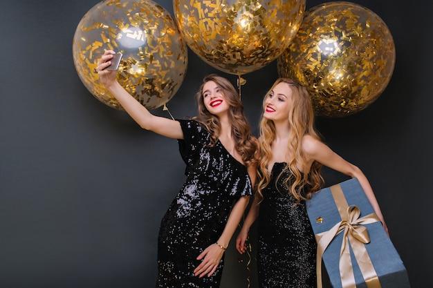 Mulher jovem rindo com penteado encaracolado, posando com prazer durante a festa. glamourosa aniversariante vestida de preto segurando uma caixa de presente grande, enquanto a amiga dela fazendo selfie.