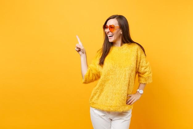 Mulher jovem rindo com suéter de pele, óculos coração laranja apontando o dedo indicador de lado no espaço da cópia isolado em fundo amarelo brilhante. emoções sinceras de pessoas, conceito de estilo de vida. área de publicidade.