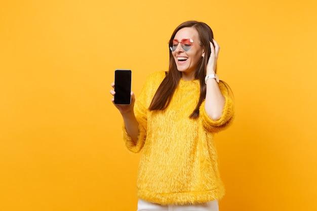 Mulher jovem rindo em copos de coração, colocando a mão na cabeça, segurando o telefone móvel com tela vazia preta em branco, isolada no fundo amarelo brilhante. estilo de vida de emoções sinceras de pessoas. área de publicidade.
