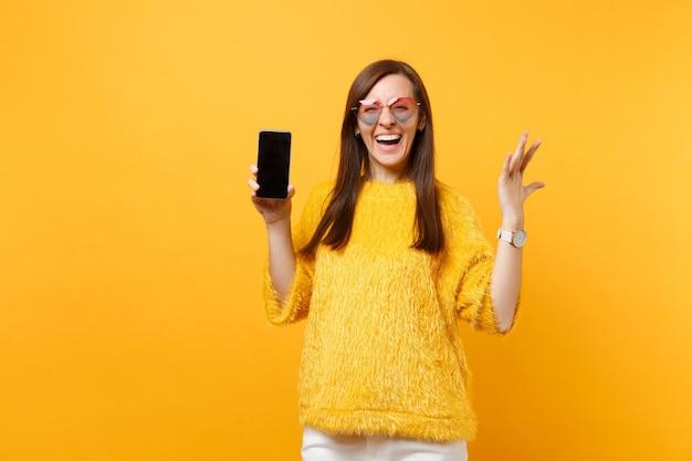 Mulher jovem rindo em copos de coração, espalhando as mãos e segurando o telefone móvel com tela vazia preta em branco, isolada no fundo amarelo brilhante. pessoas sinceras emoções, estilo de vida. área de publicidade.