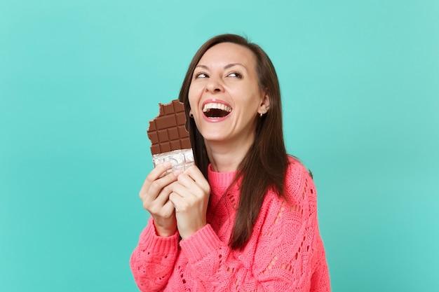 Mulher jovem rindo na camisola de malha rosa, olhando para cima, segurando na mão comendo barra de chocolate isolada no fundo da parede azul turquesa, retrato de estúdio. conceito de estilo de vida de pessoas. simule o espaço da cópia.