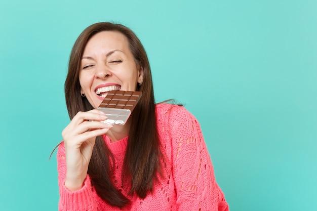 Mulher jovem rindo na camisola de malha rosa, segurando na mão, morder e comer a barra de chocolate isolada no fundo da parede azul turquesa, retrato de estúdio. conceito de estilo de vida de pessoas. simule o espaço da cópia.