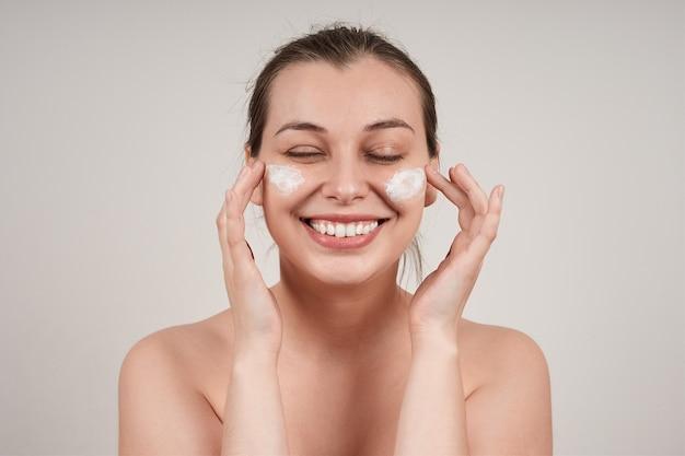Mulher jovem rindo ovely com ombros nus aplica creme nutritivo na pele do rosto, isolado na parede cinza.