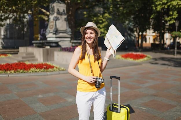 Mulher jovem rindo turista viajante com chapéu com mala, mapa da cidade, câmera fotográfica vintage retrô, andando na cidade ao ar livre. garota viajando para o exterior para viajar no fim de semana. estilo de vida da viagem de turismo.