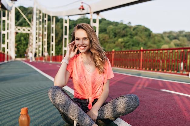 Mulher jovem romântica em camiseta rosa posando antes do treino. foto ao ar livre de modelo feminino inspirado sentado com as pernas cruzadas na pista de concreto.