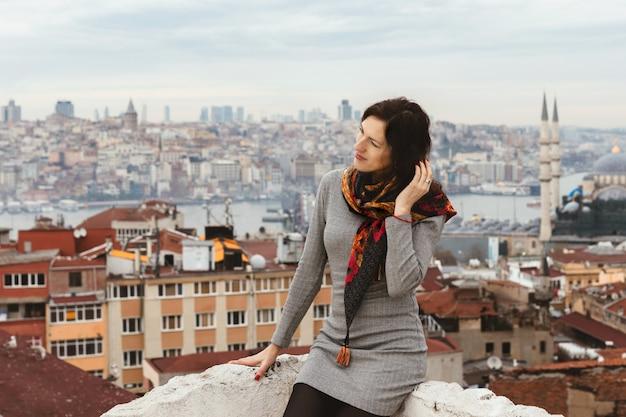 Mulher jovem romântica goza de uma vista panorâmica pitoresca de istambul do telhado.