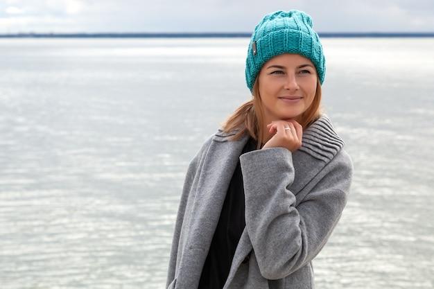 Mulher jovem romântica no fundo do mar natural azul ao ar livre. retrato de uma linda jovem morena na praia, ela tem cabelo comprido e usa casaco e chapéu de tricô