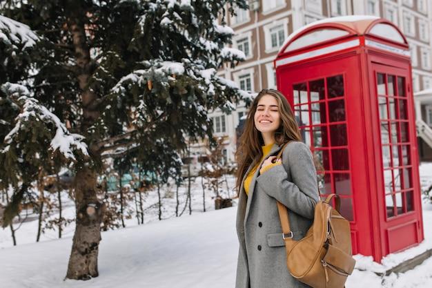 Mulher jovem romântica usa um casaco cinza, andando na rua com a caixa do telefone. retrato ao ar livre de uma mulher maravilhosa com mochila marrom, passar um tempo em winter park, perto de uma cabine telefônica.