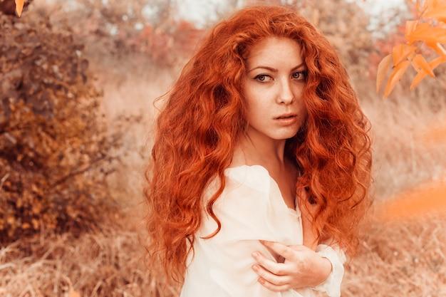 Mulher jovem ruiva bonita na floresta de outono