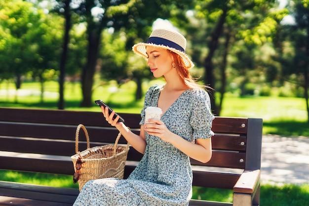 Mulher jovem ruiva bonita relaxando no banco no parque da cidade segurando café nas mãos usando p.