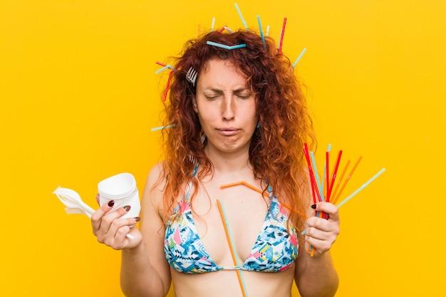Mulher jovem ruiva caucasiana irritada com o uso abusivo de plástico