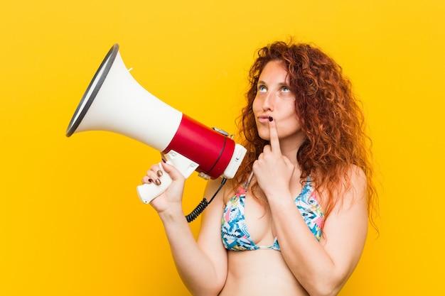 Mulher jovem ruiva caucasiana segurando um megafone