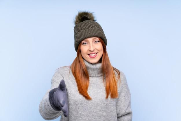 Mulher jovem ruiva com aperto de mão de chapéu de inverno depois de um bom negócio