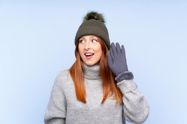 Mulher jovem ruiva com chapéu de inverno ouvindo algo
