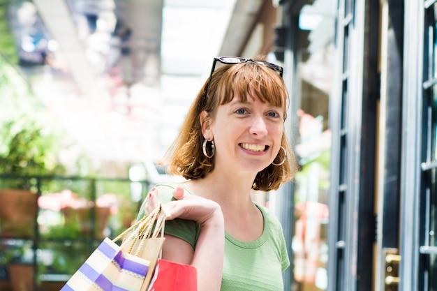 Mulher jovem ruiva com sacos de compras ao ar livre