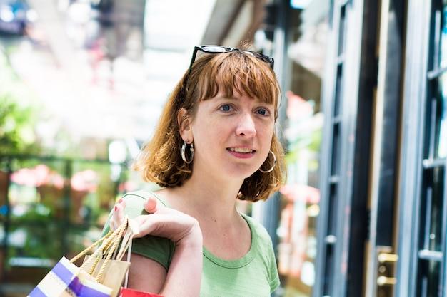 Mulher jovem ruiva com sacos de compras