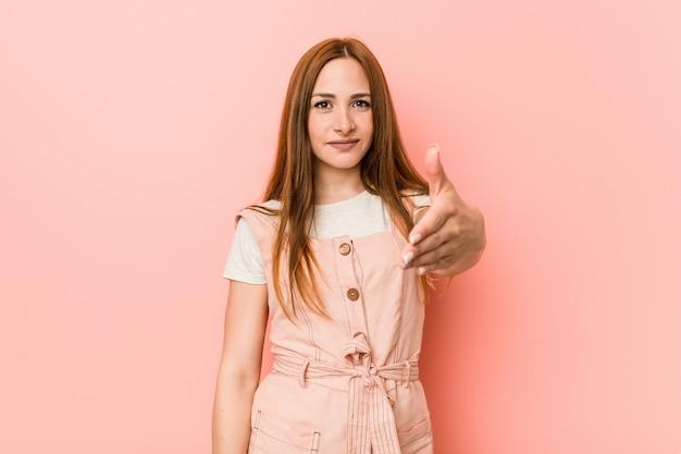Mulher jovem ruiva com sardas, esticando a mão na câmera em gesto de saudação.