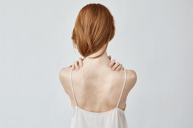 Mulher jovem ruiva com sardas posando de volta