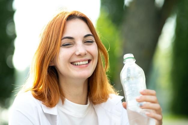 Mulher jovem ruiva com sede bebendo água de uma garrafa no parque de verão.