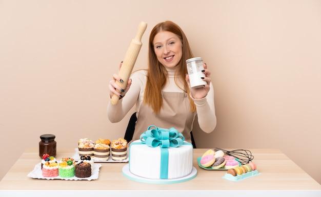 Mulher jovem ruiva com um bolo grande