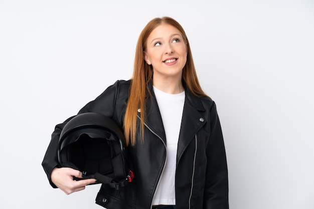 Mulher jovem ruiva com um capacete de moto sobre parede branca isolada, olhando para cima enquanto sorrindo