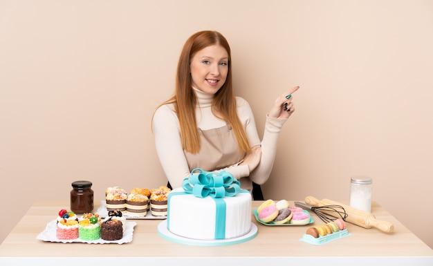 Mulher jovem ruiva com um grande bolo, apontando o dedo para o lado