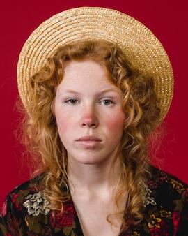 Mulher jovem ruiva de bochechas vermelhas olhando para a câmera