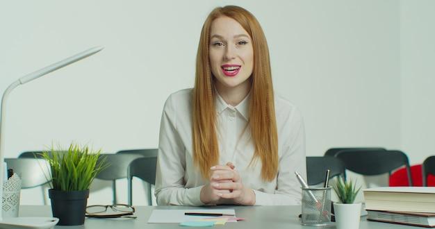 Mulher jovem ruiva de óculos tem chamada em conferência de negócios online.
