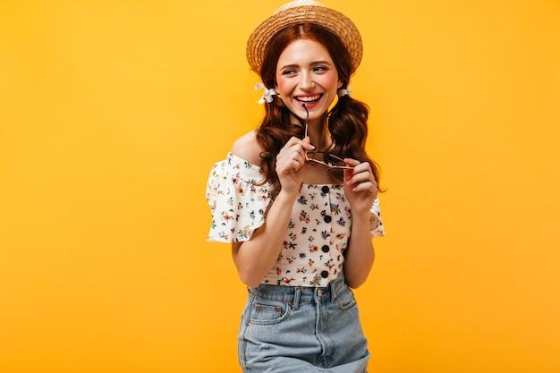 Mulher jovem ruiva de ótimo humor sorri e segura os óculos. senhora de chapéu de palha e camisa com estampa floral a desviar o olhar.