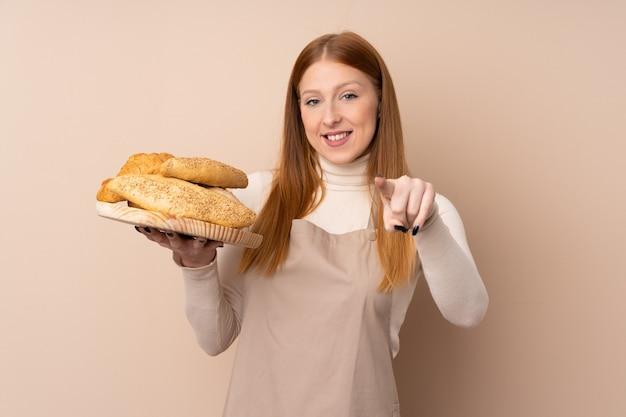 Mulher jovem ruiva de uniforme de chef. padeiro feminino segurando uma mesa com vários pães aponta o dedo para você com uma expressão confiante