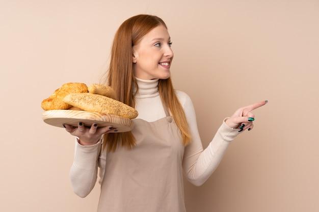 Mulher jovem ruiva de uniforme de chef. padeiro feminino segurando uma mesa com vários pães, apontando para o lado