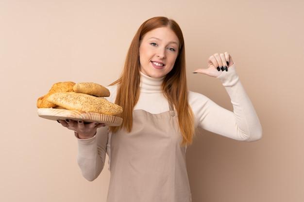 Mulher jovem ruiva de uniforme de chef. padeiro feminino segurando uma mesa com vários pães, orgulhosos e satisfeitos