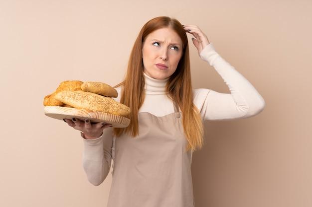 Mulher jovem ruiva de uniforme de chef. padeiro feminino segurando uma mesa com vários pães, tendo dúvidas e com a expressão do rosto confuso