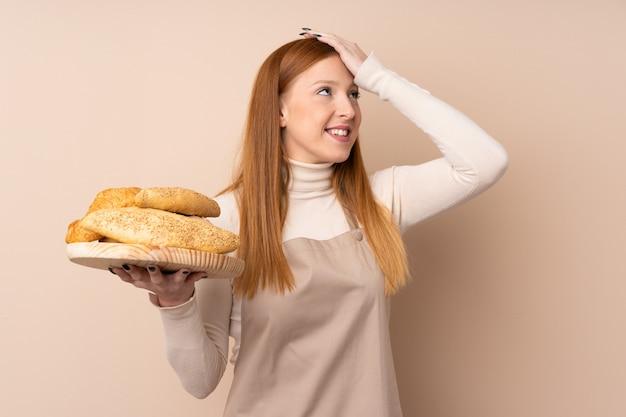 Mulher jovem ruiva de uniforme de chef. padeiro feminino segurando uma mesa com vários pães