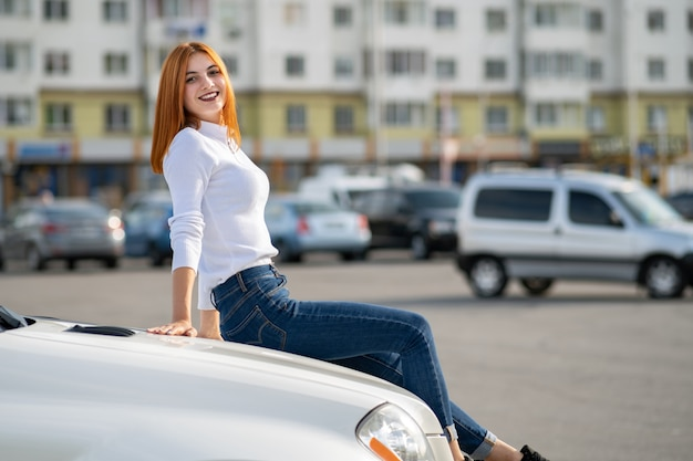 Mulher jovem ruiva elegante camisola branca, calça jeans azul elegante e tênis preto, sentado em um capô do carro novo e caro na rua da cidade, aproveitando o dia quente de verão.
