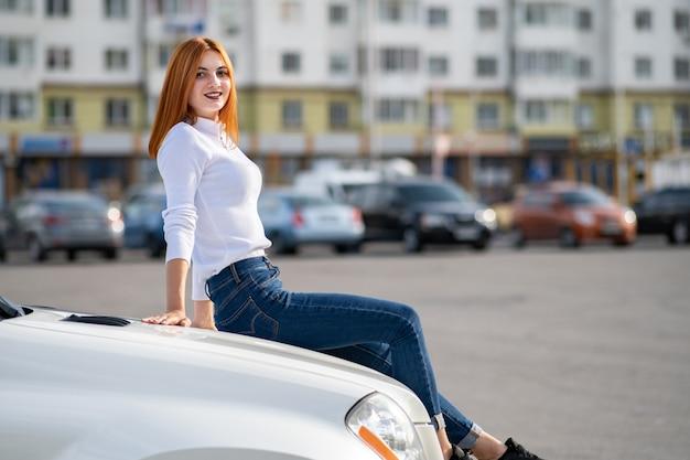 Mulher jovem ruiva elegante camisola branca, calça jeans azul elegante e tênis pretos, sentado em um capô do carro novo e caro na rua da cidade, aproveitando o dia quente de verão.