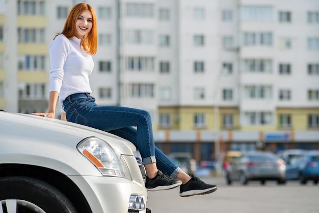 Mulher jovem ruiva elegante na camisola branca, calça jeans azul elegante e tênis preto, sentado em um capô do carro novo e caro na rua da cidade, aproveitando o dia quente de verão