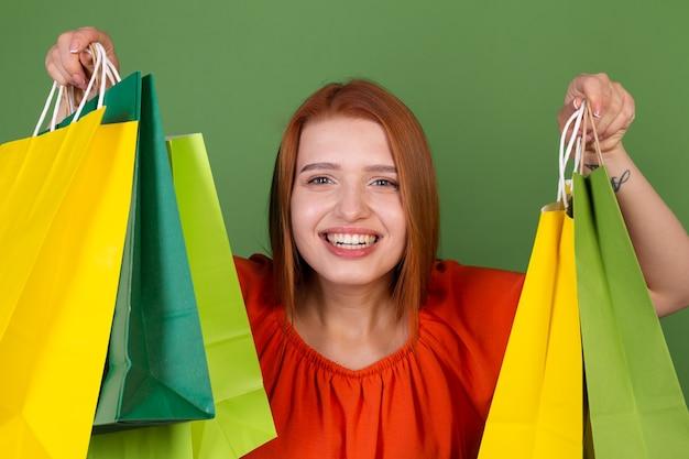 Mulher jovem ruiva em uma blusa laranja casual na parede verde com sacolas de compras.