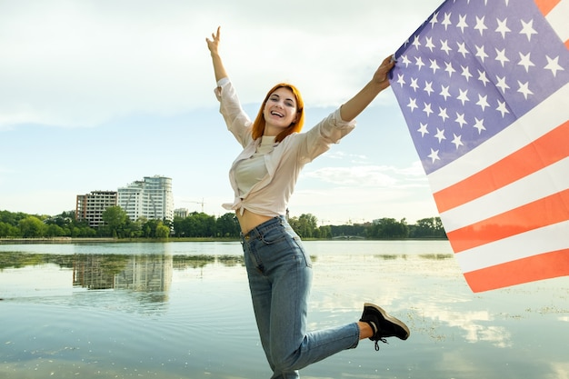 Mulher jovem ruiva feliz com a bandeira nacional dos estados unidos na mão. menina positiva comemorando o dia da independência dos eua.