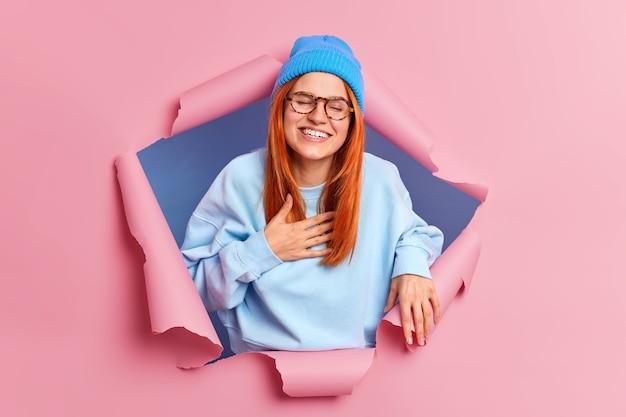 Mulher jovem ruiva feliz e sincera ri alto, sorri amplamente e não consegue parar de rir, mantém a mão no peito vestida com um traje azul elegante que atravessa a parede de papel rosa ouve anedota engraçada