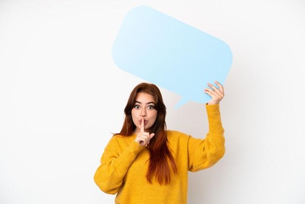 Mulher jovem ruiva isolada em um fundo branco segurando um balão de fala vazio e fazendo gesto de silêncio