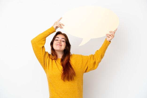 Mulher jovem ruiva isolada no fundo branco segurando um balão de fala vazio