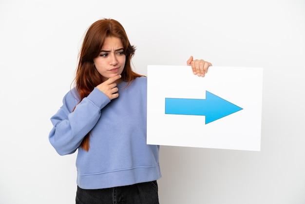 Mulher jovem ruiva isolada no fundo branco segurando um cartaz com o símbolo da seta e pensando