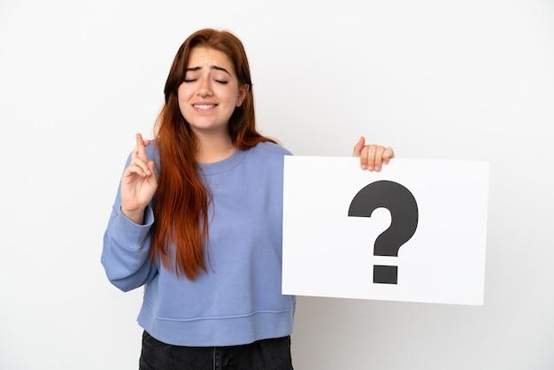 Mulher jovem ruiva isolada no fundo branco segurando um cartaz com o símbolo de ponto de interrogação e os dedos se cruzando