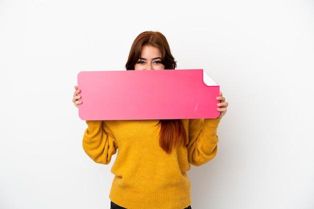 Mulher jovem ruiva isolada no fundo branco segurando um cartaz vazio e se escondendo atrás dele
