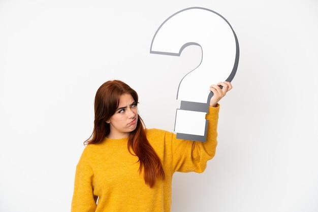 Mulher jovem ruiva isolada no fundo branco segurando um ícone de ponto de interrogação e tendo dúvidas